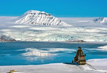 En guide som tar en pause på snøscooteren og ser ut over landskapet
