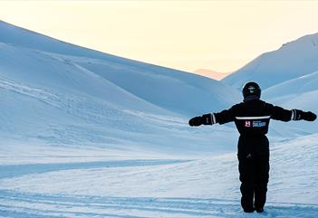 A person in snowmobile equipment looking at the landscape