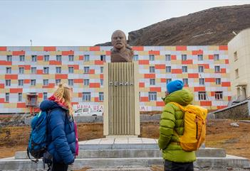Two persons looking at the Lenin statue in Barentsburg