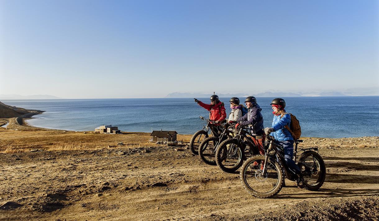 En guide og gjester på sykkel som har stoppet for å se på naturen