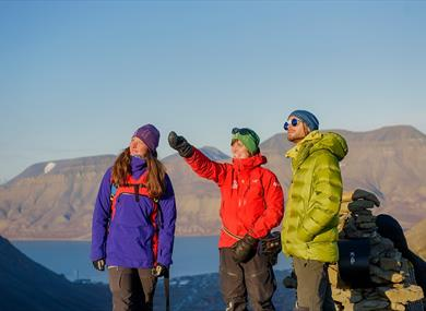 Three persons on top of a mountain