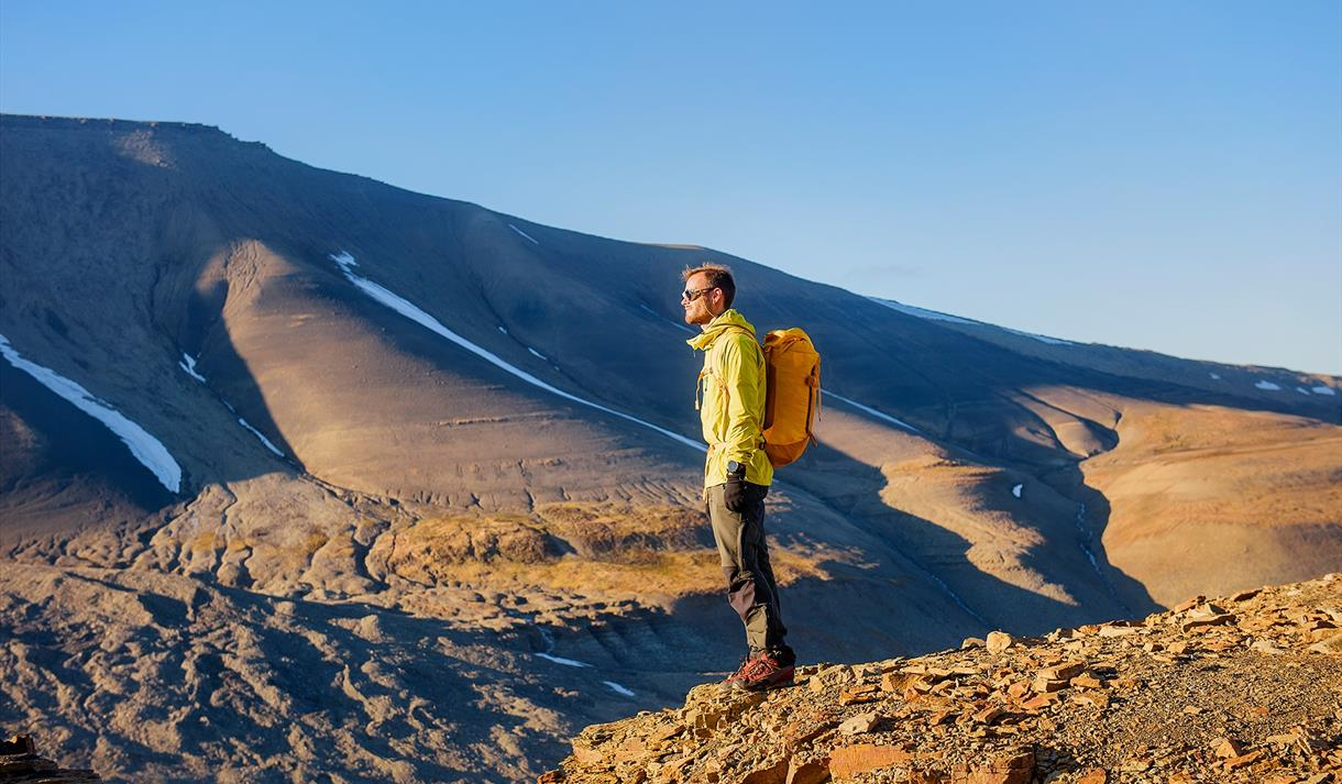 A person standing on a mountain facing the sun