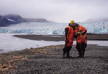 To gjester med en isbre i bakgrunnen