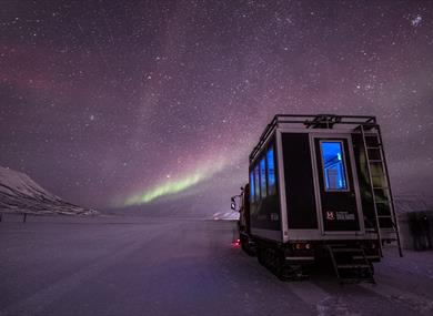 Northern Lights shining in the skies above a snowcat