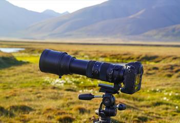 Kamera på stativ som står ute i naturen