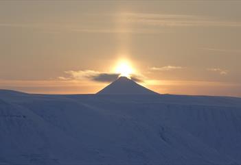 Midnattssola som skinner bak en fjelltopp