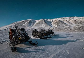 Three snowmobiles out in the wilderness beneath starry skies