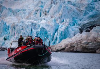 A RIB boat with persons on board sailing past a glacier