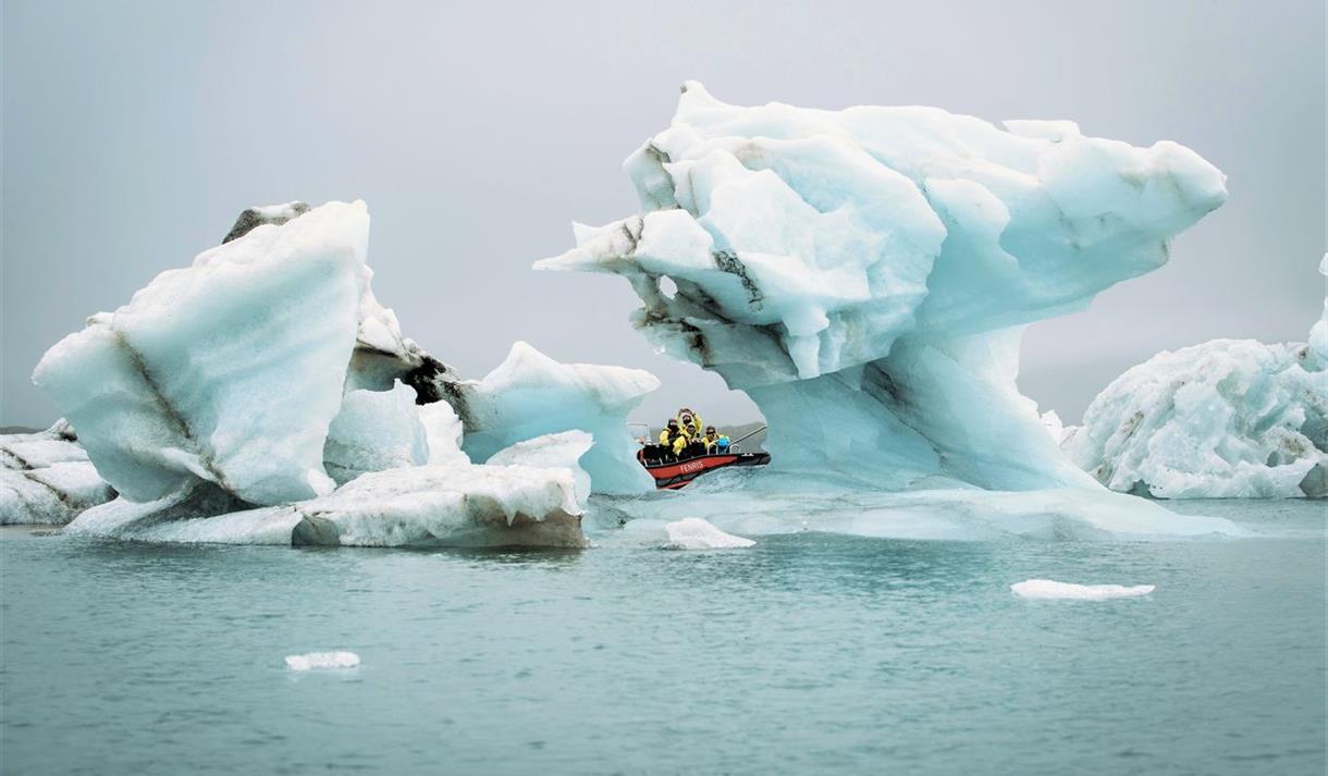En båt innimellom is som flyter i sjøen