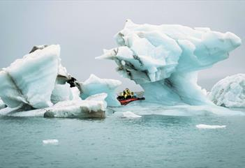 A boat in between pieces of ice floating at sea
