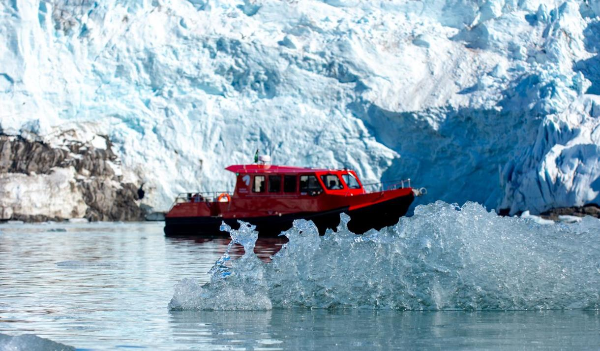 A boat in between ice floating in the sea and a glacier in the background