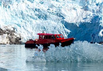 En båt mellom is som flyter i sjøen og en isbre i bakgrunnen
