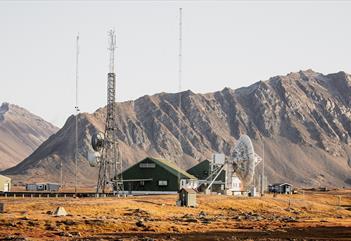 Isfjord Radio med fjell i bakgrunnen