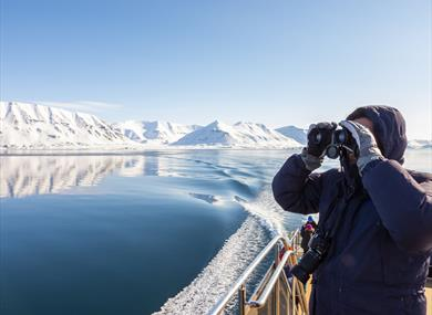 A person on board MS Bard looking out across the sea through a pair of binoculars