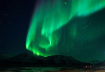 Nordlys som skinner på himmelen med mørke fjell i bakgrunnen
