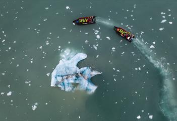 Two RIB boats sailing around an iceberg