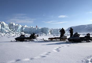 Two persons and two snowmobiles with a glacier front in the background