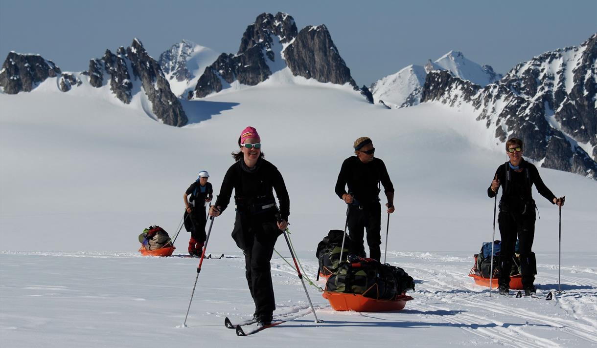 En turgruppe som drar pulker på ski