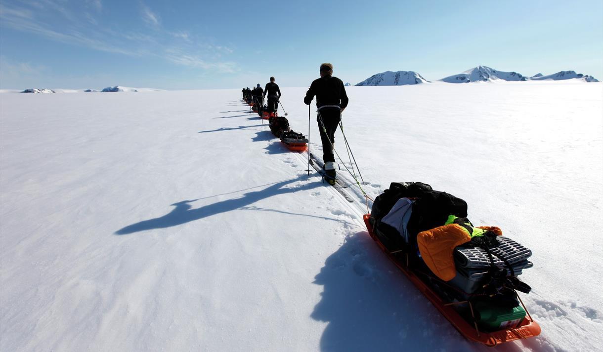 En turgruppe som trekker pulker på skitur i en rekke