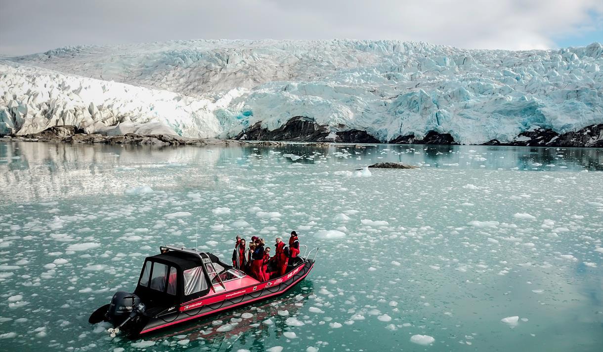 En båt med gjester om bord som seiler foran en isbre