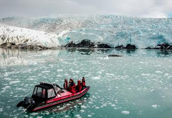 A boat with guests on board sailing in front of a glacier