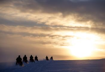 Snowmobile tour group driving towards the sun