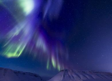 Blue and purple northern lights above the mountains