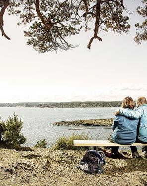 par sitter på benk ved kyststien i Grenland