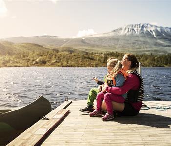 Mor og datter sitter ved innsjøen foran Gaustatoppen i Telemark