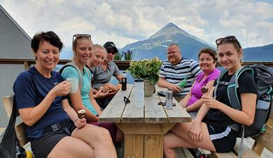 guests sitting on the terrace of Krosso Fjellstue with a view of Mount Gausta