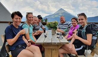 gjester som sitter på terrassen til Krosso Fjellstue med utsikt mot Gaustatoppen