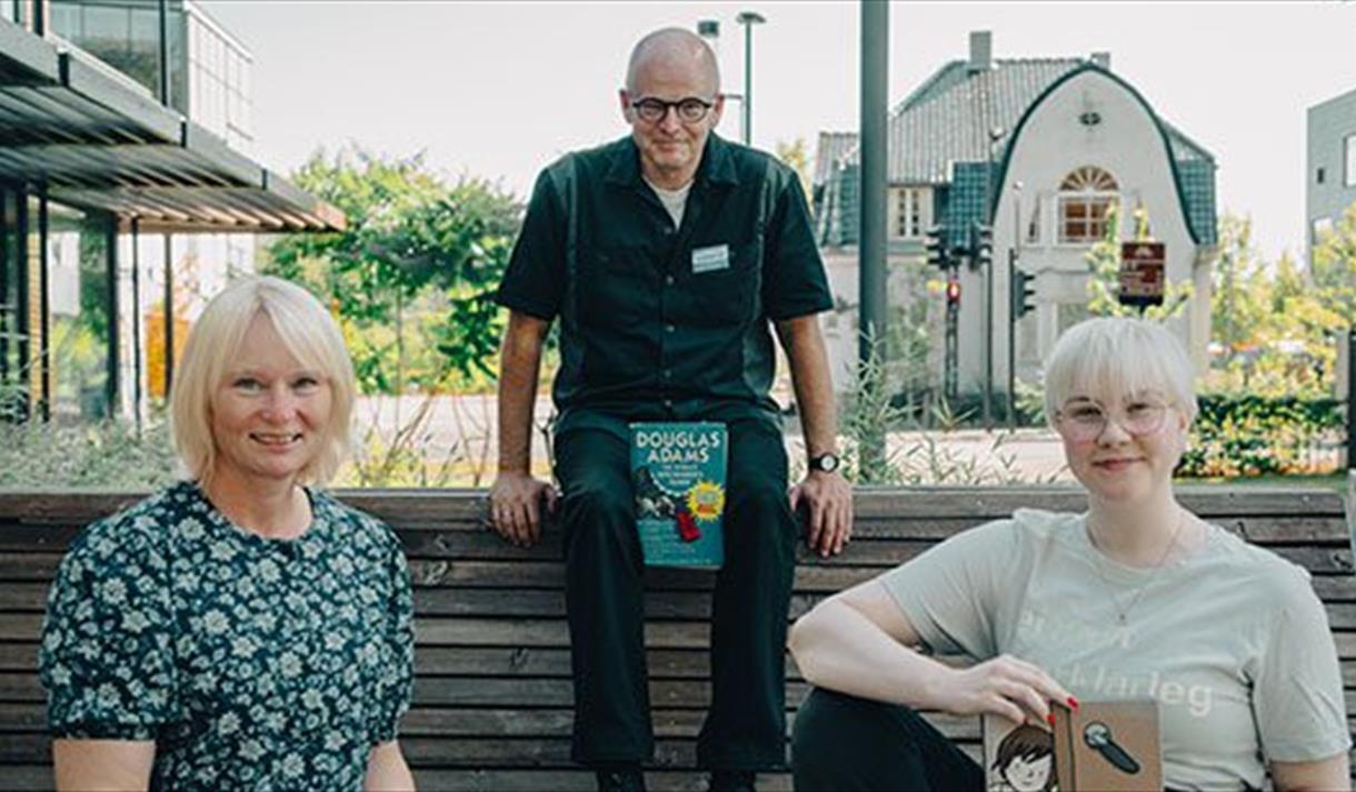 Bokpraten på Porsgrunn Bibliotek. 2 damer og en mann leser bøker