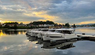 the boats from Canal Boats Telemark are located on the pier in Porsgrunn