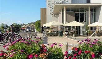 Elvespeilet Mat&Vinbar. Blomster, sykler og uteplassen på kafeen med oppslåtte parasoller. Himmelen er blå.