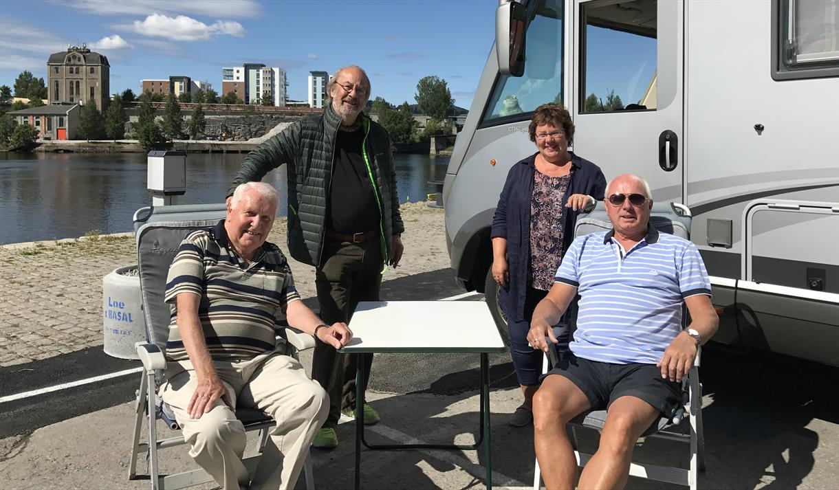 a group of elderly people are sitting next to the motorhome by the motorhome parking in Skien