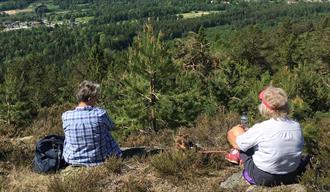 To som sitter på en høyde i naturen med fin utstikt