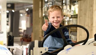 liten gutt som sitter på en porselensbil på Porsgrunds Porselænsfabrik