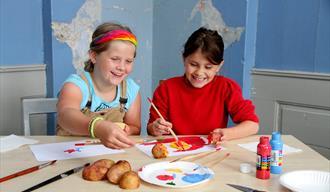 Potettrykk i Brekkeparken. To små jenter som lager potetavtrykk