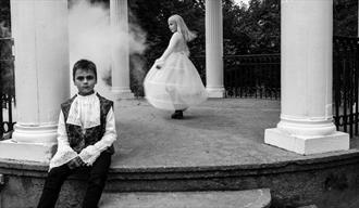 Skrekkeparken; bilde av et gutt som sitter og en jente som danser i bakgrunnen. En røyksky kommer ut fra siden.
