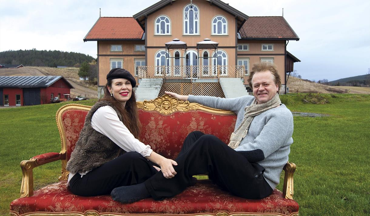the artist couple Elisabeth de Lunde and Jakob Zethners sitting on a sofa in front of Villa Lunde