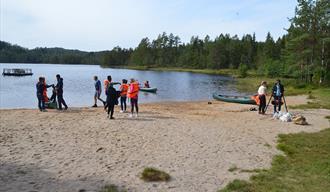 sandstrand med kano og ungdommer, flytebrygge og skogsområder