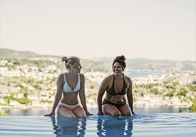 jenter som sitter på bassengkanten på utebassenget til Kragerø Resort