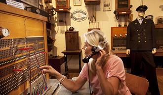 dame som sitter i en gammel telefonsentrale som utstilles på Z-museum i Nissedal