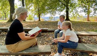 Eventyrstund i Brekkeparken. 1 dame som leser eventyr for 2 barn