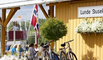 folk som sitter og spiser på Lunde Slusekro mens kanalbåten MS Henrik Ibsen seiler forbi