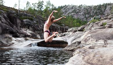 girl jumps in water in the giant pots in Nissedal