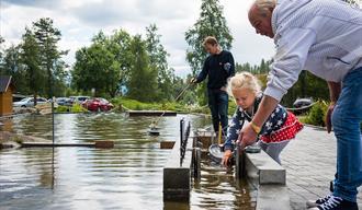 jente sluser en båt på miniatyrutgaven av telemarkskanalen på kanalparken på Vest-Telemark Museum i Eidsborg