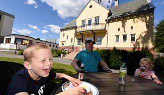 Familie koser seg på uteserveringen til Stasjonen Kafé i hydroparken, i Notodden en sommerdag. Foto