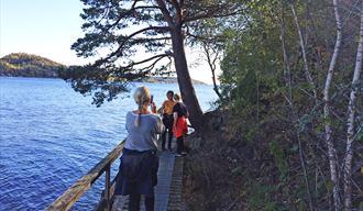 Dame tar bilde av 2 gutter på tur på kyststien fra Brevik til Skjelsvik