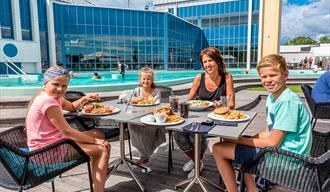 familie spiser på terrassen ved badeparken på Quality Hotel Skjærgården